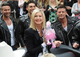 Olivia Newton-John, with Chippendales at the Rio stars Ryan Stuart, Jon Howes and Nathan Minor, makes her way to the Flamingo on Wednesday, April 2, 2014, in Las Vegas.