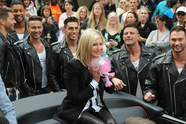 Olivia Newton-John, with Chippendales at the Rio stars Jaymes Vaughan, Matt Marshall, Ryan Stuart, Jon Howes, Nathan Minor and James Davis, makes her way to the Flamingo on Wednesday, April 2, 2014, in Las Vegas.