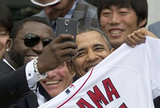 "Boston Red Sox designated hitter David ""Big Papi"" Ortiz takes a selfie with President Barack Obama, holding a Boston Red Sox jersey presented to him, during a ceremony Tuesday, April 1, 2014, on the South Lawn of the White House in Washington, where the president honored the 2013 World Series baseball champion Red Sox."