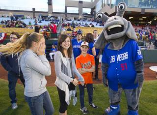 Las Vegas 51's mascot Cosmo jokes with Macy Perkes, 11, Emma Perez, 11, and Kate Perkes, 9 before the 51's season opener against the Fresno Grizzlies Thursday, April 3, 2014.