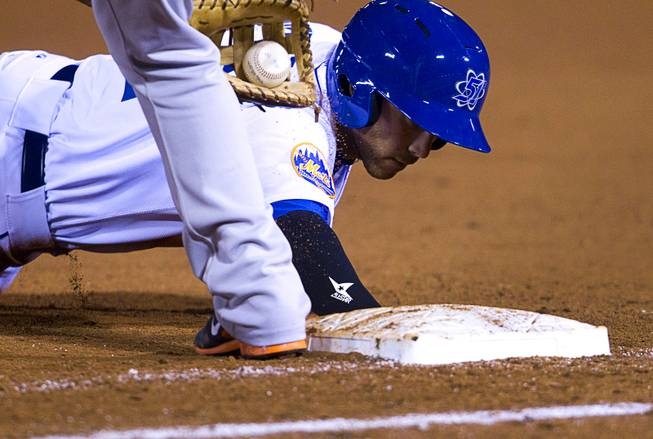 Las Vegas 51's Anthony Seratelli makes it safely back to first during a pickoff attempt in the 51's season opener against the Fresno Grizzlies Thursday, April 3, 2014.
