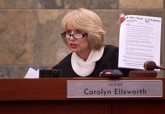 Judge Carolyn Ellsworth holds up documents during a hearing for John Michael Schaefer, a candidate for Nevada state controller, at the Regional Justice Center Thursday, April 3, 2014. Election officials want the court to remove Schaefer from the Democratic primary ballot because they contend he doesn't meet residency requirements.