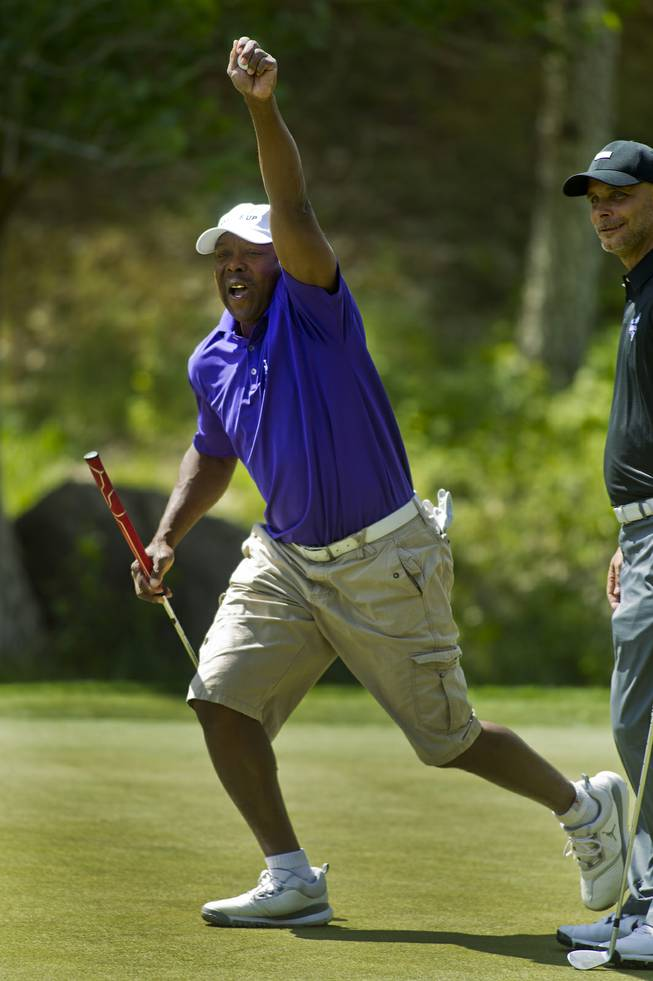 Former MLB player Vince Coleman celebrates a long putt with teammates during opening day play of the Michael Jordan Celebrity Invitational at Shadow Creek Golf Course on Thursday, April 3, 2014.