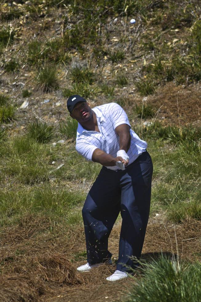 Dwight Freeney of the San Diego Chargers chips the ball from the rough during opening day play of the Michael Jordan Celebrity Invitational at Shadow Creek Golf Course on Thursday, April 3, 2014.