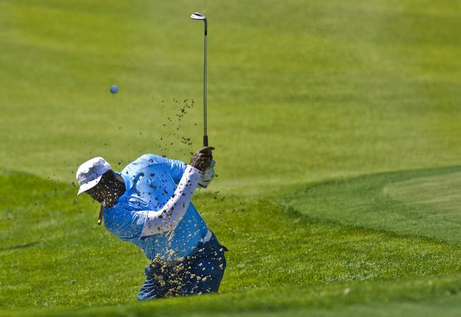 Former NBA star Michael Jordan digs the ball out of the sand during opening day play of the Michael Jordan Celebrity Invitational at Shadow Creek Golf Course on Thursday, April 3, 2014.