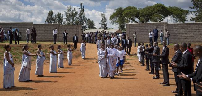 Torch-bearers carry a small flame of remembrance to a ceremony where hundreds gathered to hear genocide memories, at the Petit Seminaire school in Ndera, east of the capital Kigali, in Rwanda Thursday, April 3, 2014.
