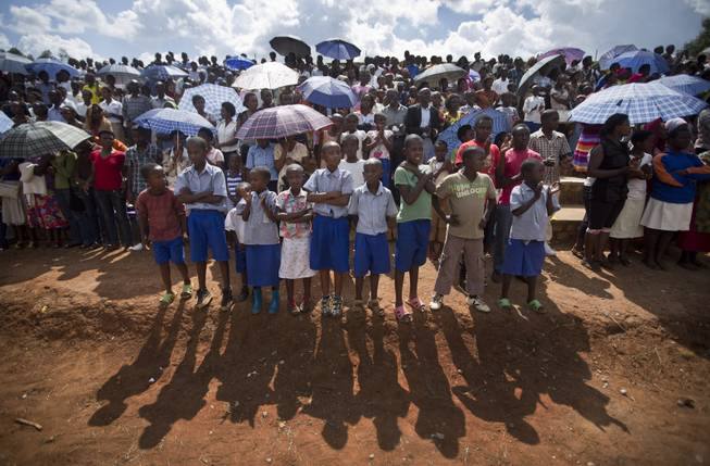Rwandan children wait for a torch ceremony where hundreds gathered for the arrival of a small flame of remembrance and to hear genocide memories, at the Petit Seminaire school in Ndera, east of the capital Kigali, in Rwanda Thursday, April 3, 2014.