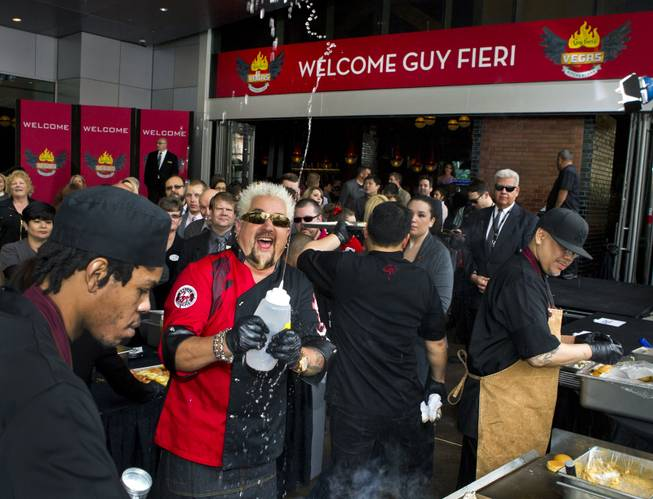 Guy Fieri squirts water in celebration while serving burgers to fans outside his first Las Vegas restaurant, Guy Fieri's Vegas Kitchen & Bar, on Friday, April 4, 2014, at the Quad.