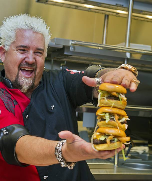 Guy Fieri shows off his signature Mac & Cheese Bacon Burger from the new kitchen of Guy Fieri's Vegas Kitchen & Bar on Friday, April 4, 2014, at the Quad. The restaurant is set to open this month.