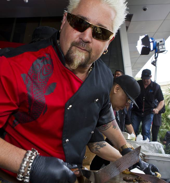 Guy Fieri works a patio grill at The Quad helping to serve burgers to fans outside his first Las Vegas restaurant, Guy Fieri's Vegas Kitchen & Bar on Friday, April 4, 2014.