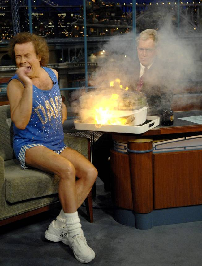 "In this photo released by CBS, author and fitness personality Richard Simmons, left, reacts to an explosion under the vegetable steamer as host David Letterman watches from the rear, on the set of the ""Late Show with David Letterman"" Wednesday, Nov. 29, 2006 in New York. This was Simmons' first appearance on the show in six years."
