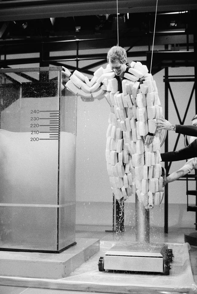 "David Letterman, host of NBC-TV's ""Late Night with David Letterman, "" is taken from a tank of water and placed onto a scale in New York while wearing a specially designed suit of sponges, Feb. 14, 1985. Letterman weighed 190 lbs. before and a whopping 500 lbs. after soaking up about 25 gallons of water, during taping for Thursday night's show."