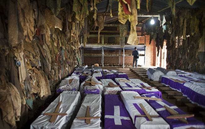 The clothes of some of those who were slaughtered as they sought refuge inside the church hang above coffins containing the remains of multiple victims, as a memorial to the thousands who were killed in and around the Catholic church during the 1994 genocide in Ntarama, Rwanda, Friday, April 4, 2014.