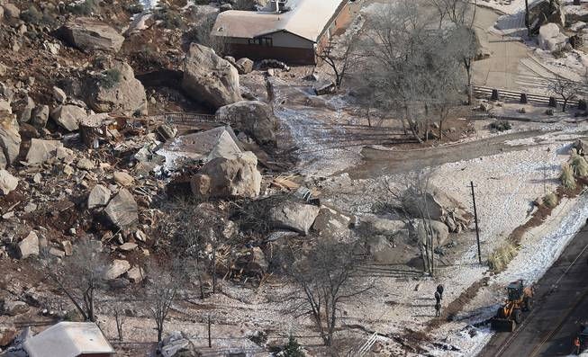 In this Dec. 13, 2013, file photo, officials survey boulders from a rock slide that crushed a home and killed two people, in Rockville, Utah.