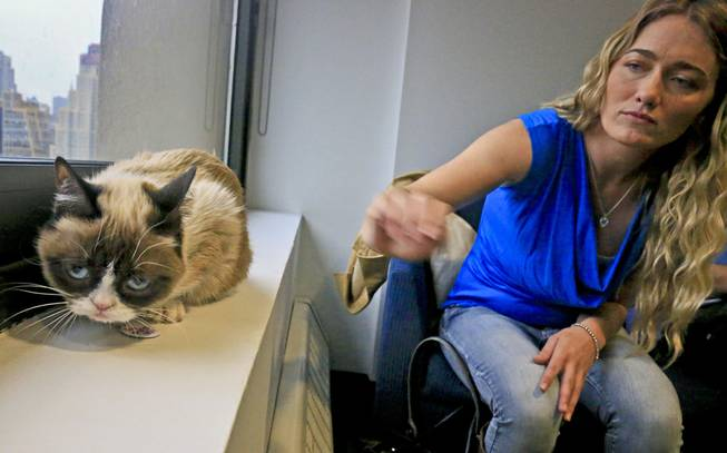 Tabatha Bundesen and her cat, Grumpy Cat, whose real name is Tardar Sauce, pose for a photograph on Friday April 4, 2014, in New York. Bundesen says that Grumpy Cat's permanently grumpy-looking face is due to feline dwarfism.