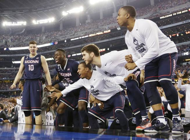 Connecticut players celebrate against Florida in the final moments of the NCAA Final Four game Saturday, April 5, 2014, in Arlington, Texas. Connecticut won 63-53.