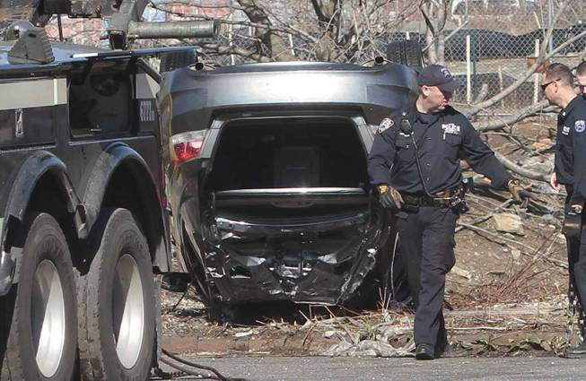 Police recover a 2009 Honda Accord that tumbled into Steinway Creek on Saturday, April 5, 2014, in New York. The driver of the car drove off a dead-end street in a desolate industrial area, flipped over a wooden curb into the East River inlet, killing four passengers.