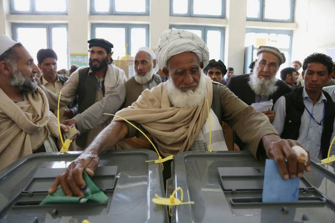 An Afghan man casts his vote at a polling station in Jalalabad, east of Kabul, Afghanistan, on Saturday, April 5, 2014. Afghan voters lined up for blocks at polling stations nationwide on Saturday, defying a threat of violence by the Taliban to cast ballots in what promises to be the nation's first democratic transfer of power. There were few instances of violence.