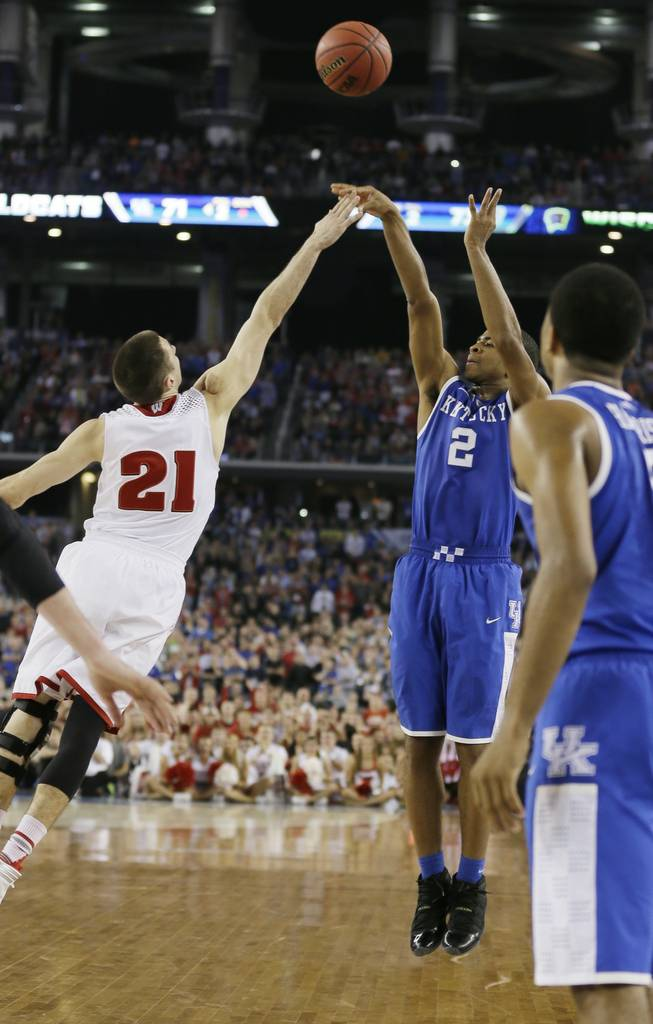 Kentucky guard Aaron Harrison makes a 3-point basket in the final seconds over Wisconsin guard Josh Gasser to win the game 74-73 on Saturday, April 5, 2014, in Arlington, Texas.