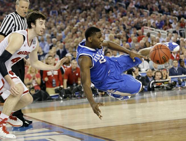 Kentucky forward Alex Poythress (22) saves the ball from going out as Wisconsin forward Frank Kaminsky (44) defends during the second half of an NCAA Final Four game Saturday, April 5, 2014, in Arlington, Texas.