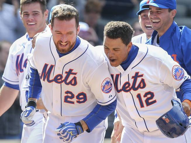 New York Mets first baseman Ike Davis (29) celebrates his walk-off grand slam in the ninth inning with center fielder Juan Lagares (12) after their game against the Cincinnati Reds at Citi Field on Saturday, April 5, 2014, in New York. The Mets won, 6-3.