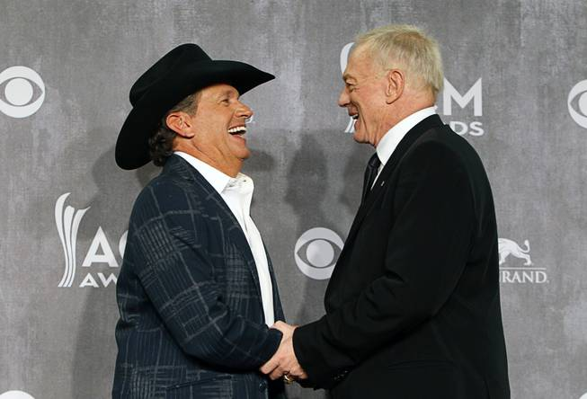 George Strait, Entertainer of the Year, greets Dallas Cowboys owner Jerry Jones in the photo room during the 49th Academy of Country Music Awards at the MGM Grand Garden Arena Sunday, April 6, 2014. The 2015 ACMA show will be held at the AT&T Stadium in Texas.