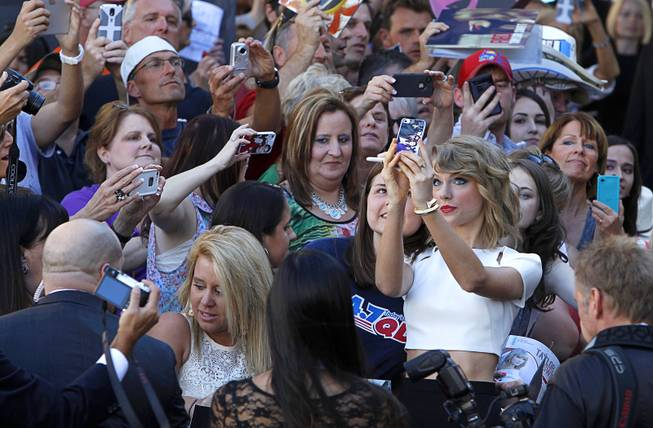 Taylor Swift takes a selfie with a fan as she arrives for the 49th Academy of Country Music Awards show at the MGM Grand Garden Arena Sunday, April 6, 2014.
