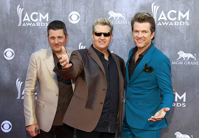 Members of Rascal Flatts, from left, Jay DeMarcus, Gary LeVox and Joe Don Rooney, arrive for the 49th Academy of Country Music Awards show at the MGM Grand Garden Arena Sunday, April 6, 2014.