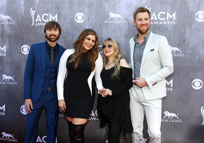 Singer Stevie Nicks, second from right, poses with members of Lady Antebellum, from left, Dave Haywood, Hillary Scott and Charles Kelley, as they arrive for the 49th Academy of Country Music Awards show at the MGM Grand Garden Arena Sunday, April 6, 2014.