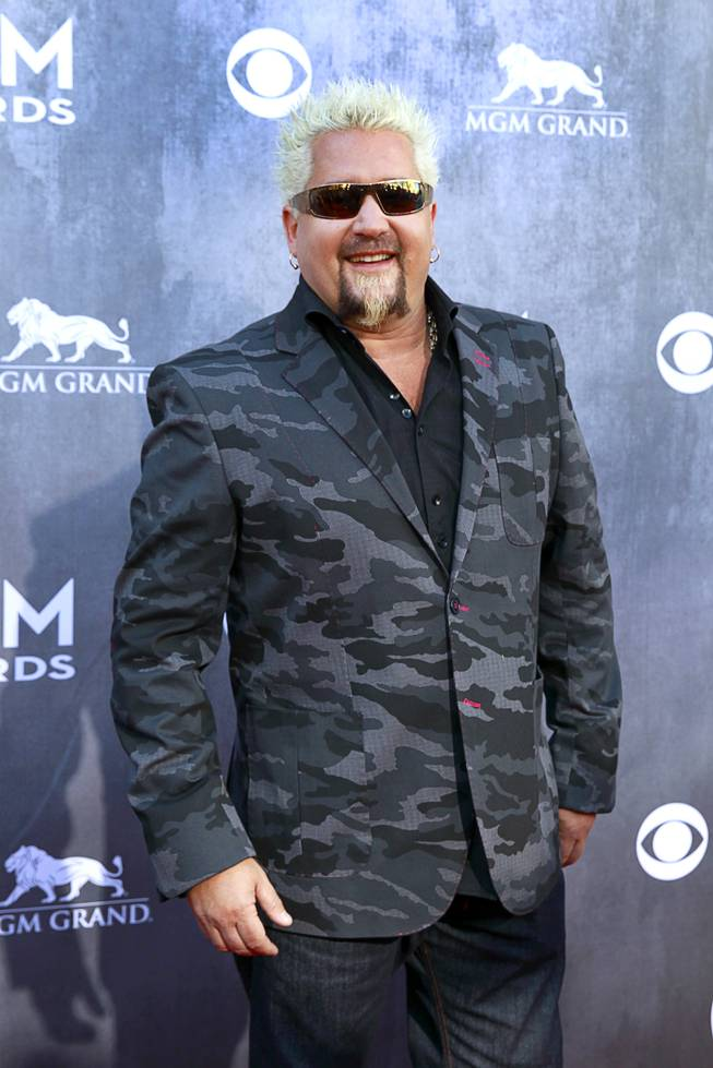 Television personality Guy Fieri arrives for the 49th Academy of Country Music Awards show at the MGM Grand Garden Arena Sunday, April 6, 2014.
