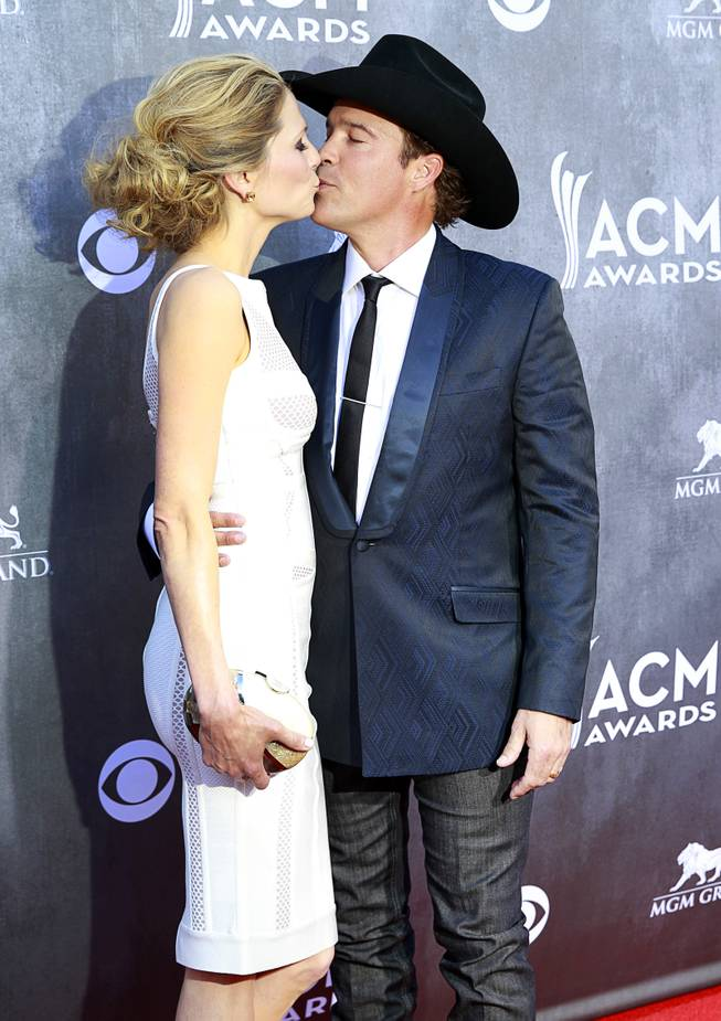 Clay Walker, right, and Jessica Craig kiss as they arrive for the 49th Academy of Country Music Awards show at the MGM Grand Garden Arena Sunday, April 6, 2014.