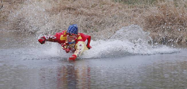 Kansas City Chiefs fan Ty Rowton, known as XFactor, takes a Plunge for Landon in a farm pond near Bonner Springs, Kan., Friday, April 4, 2014. A 5-month-old boy's battle with cancer has inspired hundreds to jump into cold bodies of water, from a local golf course pond to the Gulf of Mexico and even the Potomac River in Washington, D.C.
