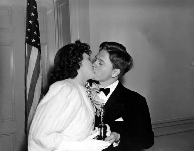 Judy Garland receives a kiss from Mickey Rooney as she is given a special award Oscar for her outstanding performance as a screen juvenile during the past years at the 1939 Academy Awards presented at the Ambassador Hotel, Los Angeles, Ca., Feb. 29, 1940.