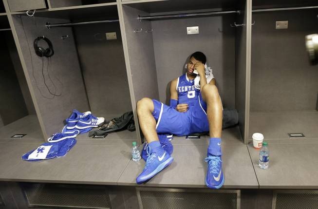 Kentucky guard Andrew Harrison sits in the locker room after his team's 60-54 loss to Connecticut in the NCAA Final Four tournament college basketball championship game Monday, April 7, 2014, in Arlington, Texas.