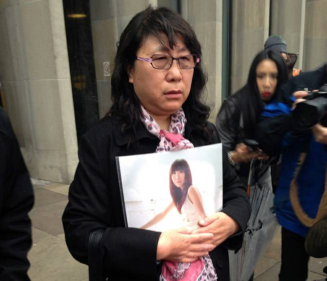 Ya Ru Zheng holds a photo of her daughter Qian Liu outside a courthouse in Toronto, on Monday, April 7, 2014. A jury has found 32-year-old Brian Dickson guilty of first-degree murder in the death of York University student Liu, from China.