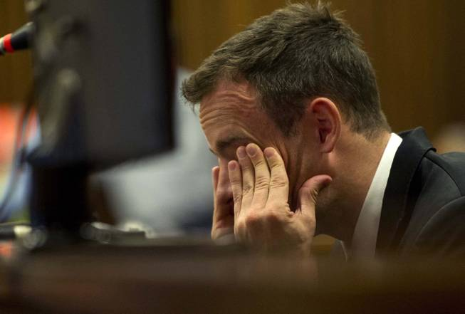 Oscar Pistorius reacts as he listens to evidence by a pathologist in court in Pretoria, South Africa, Monday, April 7, 2014.