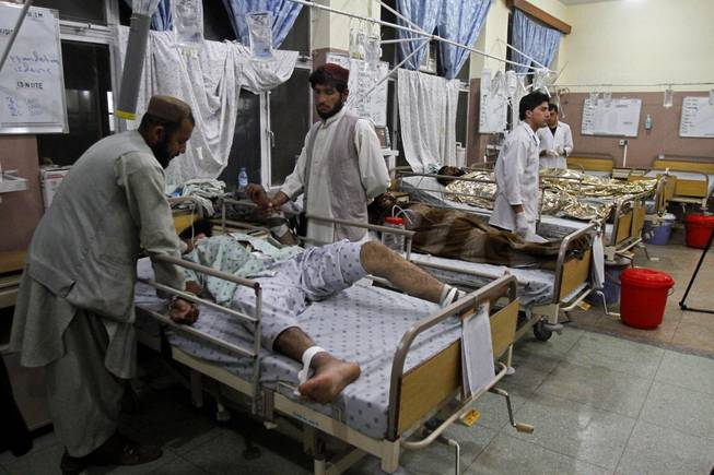 Family members help a wounded man at a hospital after a roadside bomb in Kandahar, south of Kabul, Afghanistan, Monday, April 7, 2014. A roadside bomb killed at least 15 people traveling in vehicles that had been diverted from a main road Monday after an earlier attack in southern Afghanistan, officials said.