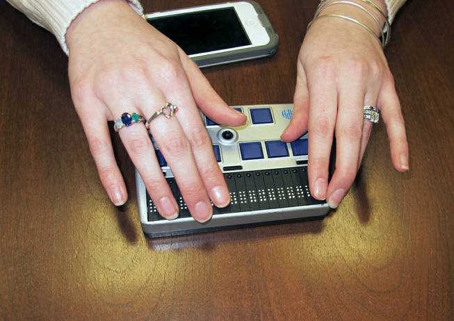 Megan Dausch, an instructor at the Helen Keller National Center, demonstrates the use of a Braille reader that helps blind clients access the Internet, in Sands Point, N.Y., March 26, 2014.