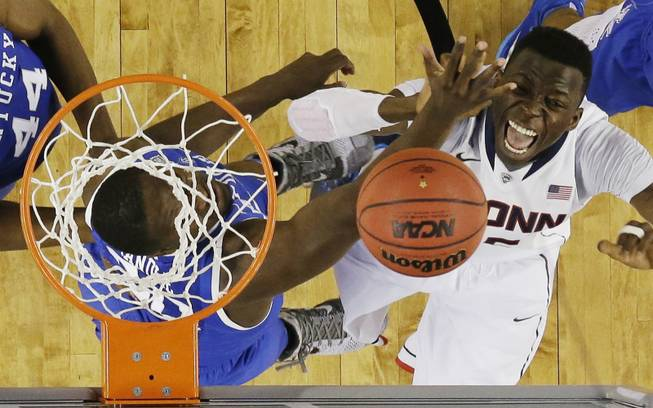 Kentucky forward Julius Randle, left, and Connecticut center Amida Brimah go after the ball during the second half of the NCAA Final Four tournament college basketball championship game Monday, April 7, 2014, in Arlington, Texas. (AP Photo/David J. Phillip)