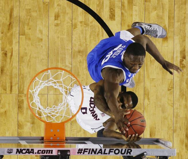 Kentucky forward Julius Randle (30) tries to block the ball from Connecticut forward Phillip Nolan (0) during the first half of the NCAA Final Four tournament college basketball championship game Monday, April 7, 2014, in Arlington, Texas. (AP Photo/David J. Phillip)