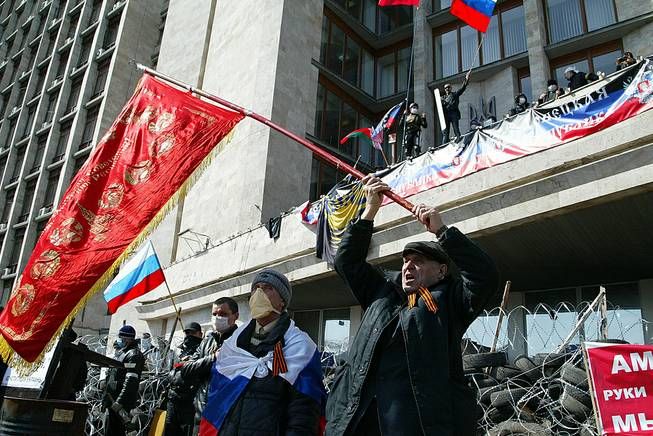 Activists wave an old Soviet and Russian national flags in front of a barricade at the regional administration building, in Donetsk, Ukraine, Monday, April 7, 2014.