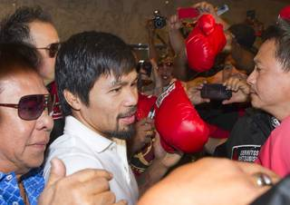 Boxer Manny Pacquiao of the Philippines and his entourage push though media and fans as he arrives at the MGM Grand on Tuesday, April 8, 2014. Pacquiao will challenge undefeated WBO welterweight champion Timothy Bradley at the MGM Grand Garden Arena on Saturday. The fight is a rematch of their bout June 9, 2012, which Bradley won.