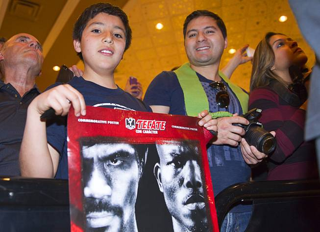 Alan Jaimes, 11, and his father Francisco Jaimes of Georgia wait for boxer Manny Pacquiao of the Philippines at the MGM Grand Tuesday, April 8, 2014. Pacquiao will challenge undefeated WBO welterweight champion Timothy Bradley at the MGM Grand Garden Arena on Saturday. The fight is a rematch to a June 9, 2012 fight that Bradley won.