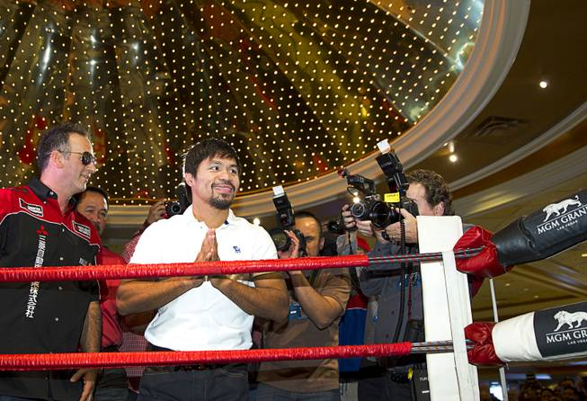 Boxer Manny Pacquiao of the Philippines acknowledges fans from a ring in the lobby of the MGM Grand Tuesday, April 8, 2014. Pacquiao will challenge undefeated WBO welterweight champion Timothy Bradley at the MGM Grand Garden Arena on Saturday. The fight is a rematch to a June 9, 2012 fight that Bradley won.