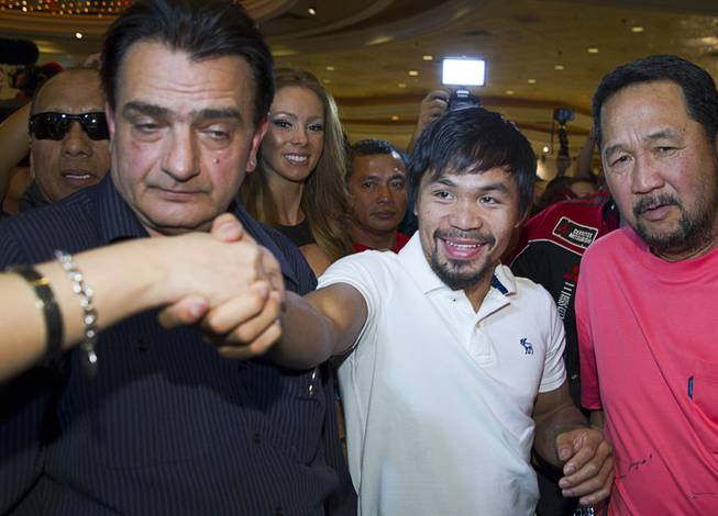 Boxer Manny Pacquiao of the Philippines greets a fan as he makes his official arrival at the MGM Grand Tuesday, April 8, 2014. Pacquiao will challenge undefeated WBO welterweight champion Timothy Bradley at the MGM Grand Garden Arena on Saturday. The fight is a rematch to a June 9, 2012 fight that Bradley won.