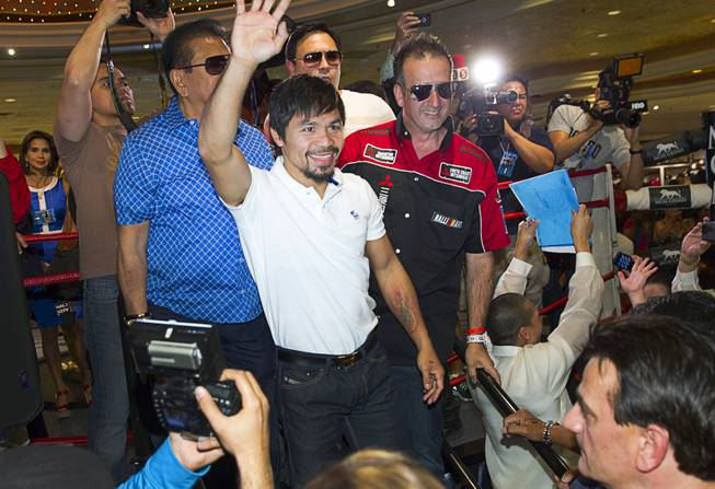 Boxer Manny Pacquiao of the Philippines waves to fans from a ring in the lobby of the MGM Grand Tuesday, April 8, 2014. Pacquiao will challenge undefeated WBO welterweight champion Timothy Bradley at the MGM Grand Garden Arena on Saturday. The fight is a rematch to a June 9, 2012 fight that Bradley won.