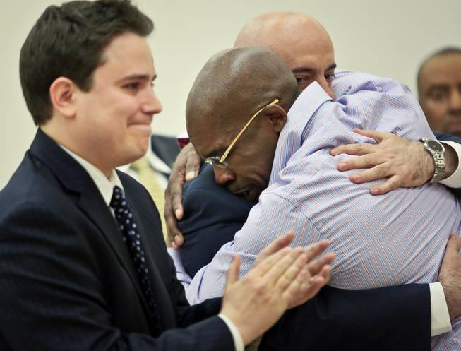 Jonathan Fleming hugs his attorney Anthony Mayol while his other attorney Taylor Koss applaud in Brooklyn's Supreme Court, after a judge declared him a free man on Tuesday April 8, 2014 in New York. Fleming, who spent almost a quarter-century behind bars for murder, was cleared of a killing that happened when he was 1,100 miles away on a Disney World vacation in 1989.