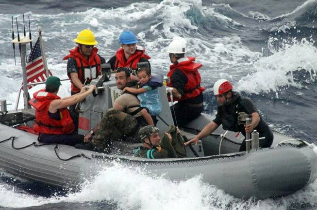 Sailors from Oliver Hazard Perry-class frigate USS Vandegrift (FFG 49) assist in the rescue of a family with a sick infant via the ship's small boat as part of a joint U.S. Navy, Coast Guard and California Air National Guard rescue effort, Sunday, April 6, 2014.