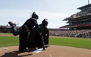 Miles Scott, dressed as Batkid, left, throws the ceremonial first pitch next to Batman before an opening day baseball game between the San Francisco Giants and the Arizona Diamondbacks in San Francisco, Tuesday, April 8, 2014. On Nov. 15, 2013, Scott, a Northern California boy with leukemia, fought villains and rescued a damsel in distress as a caped crusader through The Greater Bay Area Make-A-Wish Foundation.