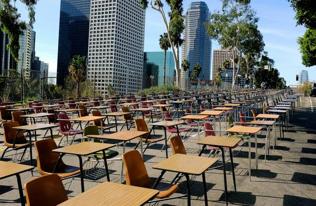 School desks placed by parents, district graduates and activists block a street in front of Los Angeles Unified School District headquarters in a demonstration against student dropout rates Tuesday, April 8, 2014, in downtown Los Angeles.
